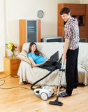 Man cleaning  while woman lying with notebook Royalty Free Stock Image