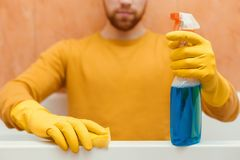 Man cleans bathroom with sponge and cleaning products stock images