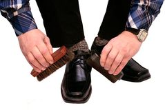 The man cleans boots. Is isolated on a white background Royalty Free Stock Photos