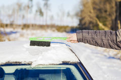 Man cleans with brush the car out of the snow Royalty Free Stock Photo
