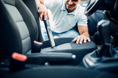 Man cleans car interior with vacuum cleaner Royalty Free Stock Image