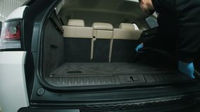 Man cleans the car interior with vacuum cleaner, dry cleaning of trunk. Close up stock video