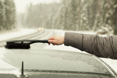 Man cleans the car out of the snow Royalty Free Stock Image
