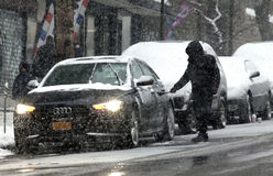 Man cleans car during snow storm Stock Photos