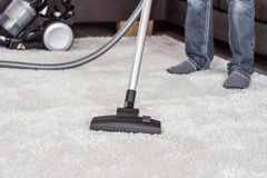 A man cleans the carpet with a vacuum cleaner. Closeup of the head of a modern vacuum cleaner used when vacuuming einens thick white carpet, in the background Royalty Free Stock Images