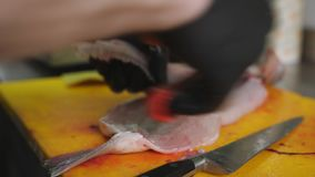 A man cleans the fish fillets from the bones. Man pulls out the bones from fish fillets with tweezers. The chef in the kitchen physical the inside of the fish stock video footage