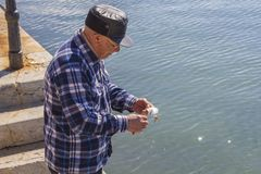 Man cleans fish on the pier Royalty Free Stock Images