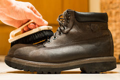 Man cleans gray leather shoes closeup. Cleaning brush and leather boots close-up Stock Images