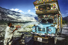 Man cleans his overland truck with water from a creek Stock Image