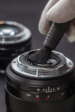 Man cleans the lens from accumulated dirt and dust Stock Photography