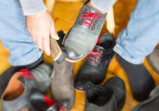 A man cleans the shoes with a brush Stock Photography