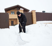 Man cleans snow around the house Stock Image
