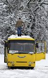 The man cleans snow from a bus roof after snowfall Stock Photos
