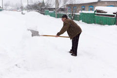 Man cleans snow shovel Royalty Free Stock Photos