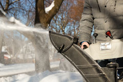 A man cleans snow from sidewalks with snowblower. Royalty Free Stock Image