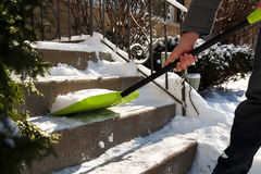 A man cleans snow from sidewalks with snowblower. Royalty Free Stock Photos