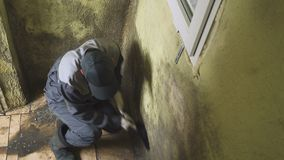 The man cleans the walls of strong dirt with a brush and a rag. The worker washes the corridor walls manually. Mold and