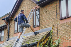 Man cleans window of an old house Royalty Free Stock Photos