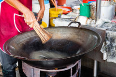 Man cleans wok at Kimberly Street Food Night Market. GEORGE TOWN, MALAYSIA - MARCH 23: Man cleans wok at Kimberly Street Food Night Market on March 23, 2016 in Royalty Free Stock Images