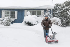Man clearing driveway with snowblower. Man using snowblower to clear deep snow on driveway near residential house after heavy snowfall royalty free stock photo