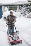 Man clearing driveway with snowblower. Man using snowblower to clear deep snow on driveway near residential house after heavy snowfall stock photos