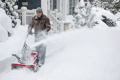 Man clearing driveway with snowblower. Man using snowblower to clear deep snow on driveway near residential house after heavy snowfall Stock Photo