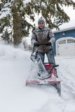 Man clearing driveway with snowblower. Man using snowblower to clear deep snow on driveway near residential house after heavy snowfall royalty free stock photos