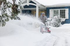 Man clearing driveway with snowblower. Man using snowblower to clear deep snow on driveway near residential house after heavy snowfall stock image