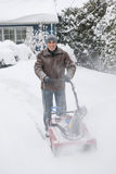 Man clearing driveway with snowblower. Man using snowblower to clear deep snow on driveway near residential house after heavy snowfall royalty free stock images
