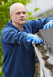 Man Clearing Leaves From Guttering Of House Royalty Free Stock Photo