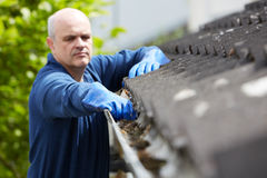 Man Clearing Leaves From Guttering Of House Royalty Free Stock Photos