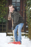Man Clearing Snow Covered Path Outside Home Stock Photo