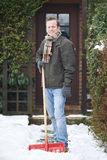 Man Clearing Snow Covered Path Outside Home Stock Photos