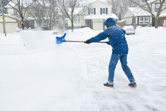 Man Clearing Snow in the Driveway Stock Images