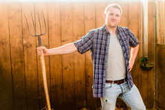 Man clearing stable with pitchfork Royalty Free Stock Photo