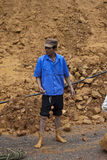 Man clears a road. NORTHERN LAOS - AUGUST 14: Man clears a road after landslide on August 14, 2012 in Northern Laos. Landslides are common in Laos because annual Stock Images