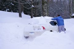 Man clears snow from car after storm stock photos