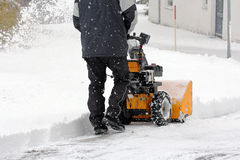 Man clears snow with a snow mill Royalty Free Stock Photo