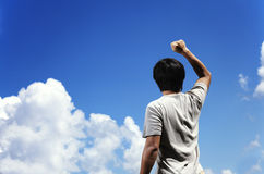 Man clench fist facing the sky. Man clench fist facing the blue sky royalty free stock image