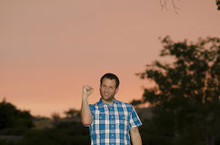 Man with a clenched fist outdoors at sunset. Stock Images