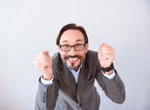 Man clenching fists in gesture of success. It is my chance. Joyful mature man clenching fists in gesture of a success while standing isolated on the grey Royalty Free Stock Images