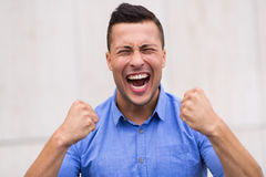 Man clenching fists. Handsome young man screaming outdoors Royalty Free Stock Images