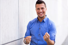 Man clenching fists. Handsome young man smiling outdoors Royalty Free Stock Photography