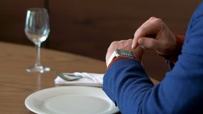 Man clicking on screen smart watch for setting mobile app at table in restaurant stock video