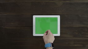 Man clicking on a tablet with greenscreen stock footage