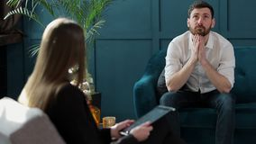 Man client sitting with female psychologist on the comfortable couch during the psychological session at the blue office