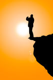 Man on the cliff. With sun background Stock Image