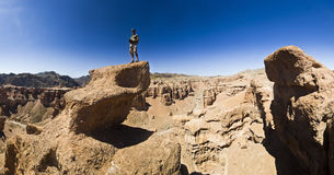 Man on a cliff in desert canyon Stock Image