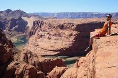 Man on cliff edge. Horizontal image of a man sitting on the edge of a sandstone cliff overlooking Glen Canyon, Arizona Stock Photos