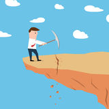 Man on a cliff edge digging the ground Stock Photos